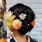 帯に合わせてオレンジ系の花で華やかに(石井)